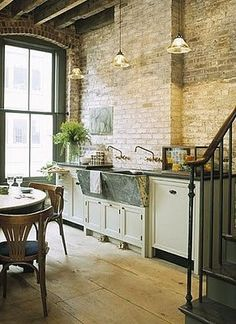 Kitchen with exposed brick wall, farmhouse sink, and a rustic industrial but clean feel.
