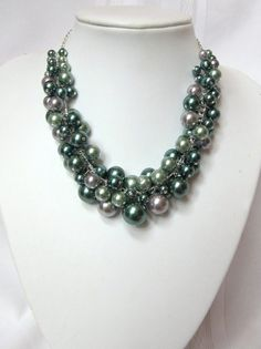 This lovely Shades of Green and Silver multi-color glass pearl cluster necklace will add a touch of beauty to any outfit from casual to elegant. Goes from jeans to gowns! This is a very full and fun necklace. This necklace is adjustable in length from 15 up to 20. Pearls are glossy finished in silver and a range of light sage green to dark blue-green / teal colors in various sizes from 6mm to 16mm. Each pearl was hand wired to the adjustable length silver plated double curb chain. This i...