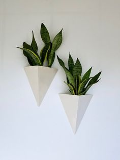 This modern planter box will add a pop of color and life as non-traditional wall decor. Use it as a vase or planter. The geometric triangle ceramic design looks beautiful from all angles.  Size: 11 tall x 9 wide  Opening measures 9 x 6.5 x 6.5  Exterior features a white glaze, inside is unglazed porcelain. Hangs from the 2 holds in the back of the planter.  *Plants not included. **Listing is for ONE Planter  Please note, this product is currently experiencing a 2 week production lead time.