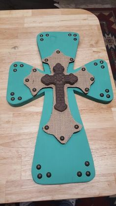 New cross design  This cross is 18 inches tall and 11.5 inches wide. The bottom layer is painted in turquoise and with buttons around corners. The top cross is painted black with burlap on top. The third cross is metal These can be painted to your color liking and can be in any color combination. It will have hanger on the back.