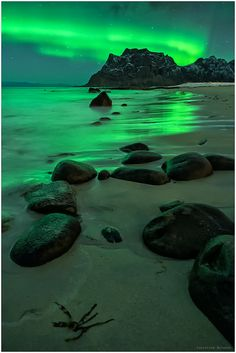This shows the actual colors you see in the sky: Northern Lights On The Beach, Uttakleiv, Lofoten, Norway by Christian Bothner.