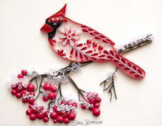 A quilled northern cardinal sitting on a berry branch covered in snow made by quilling artist Stacy Bettencourt, owner of Mainely Quilling in Jefferson, ME.