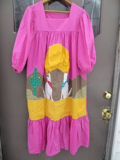 good condition  80s Mexican cotton embroidered dress /MUU MUU   desert scene //cactus  large embroidered desert and coyotes dress  oversized ....med  hot pink cotton with desert scene front RUFFLED SKIRT AT BOTTOM tag..MADE IN mexico  BY mINERVA  MEASURES  BUST....48  LENGTH..45