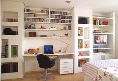 O móvel é dividido em um home office e uma estante para TV. Na área de trabalho, que está localizada dentro do quarto, luminária, objetos de escritório e cadeira de couro. As prateleiras são de MDF com pintura texturizada branca