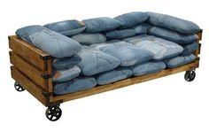 Pallet couch on wheels with denim pillows.