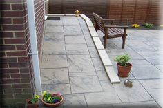 Pattern Imprinted Concrete ramp. If we got the pool deck done new, we could make part of it a ramp to the higher part of the back yard (to allow the lawnmower to go there) and the ramp could be flanked by the retaining walls with built-in planters.