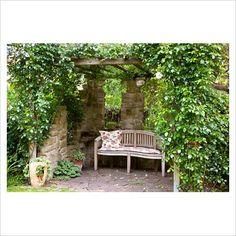 Pergola with climbing shrubs surrounding a seating area.  Love hidden area's in the garden