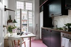 Black kitchen with a pink floor