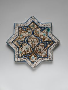 Eight-pointed Star Tile Depicting Animals Date: A.H. 665/ A.D. 1267 - Iran, Kashan Medium: Stonepaste; luster-painted on opaque white glaze under transparent glaze Dimensions: W. 8 in. (20.3 cm)