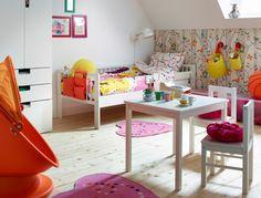 Cameretta con letto bianco e copripiumino e federa colorati. Tappeti arancione/giallo, poltrona girevole con capote e tavolo con sedie bianchi.