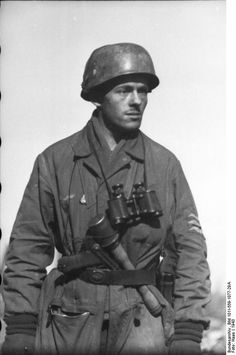 Fallschirmjäger (paratrooper) with stick grenade, Zeiss binoculars, and a Luger 9 mm tacked in his belt. The Luger, contrary to public impression, was not a widely distributed sidearm, being reserved for higher officer ranks only. Hence, it was a valued trophy for  Allied soldiers. Spring 1943, central Russia.