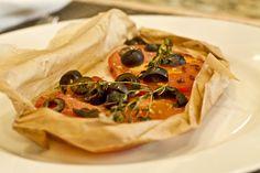 Pescados cocinados en papel de cera con tomates, tomillo y aceitunas.