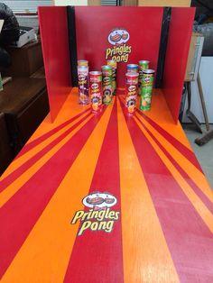 An old office desk from a charity shop, some brightly coloured paint and empty Pringle cans made this interesting Ping Pong ball game. If you want the logo (which I simply printed on a laser printer and cut round) send me a message!
