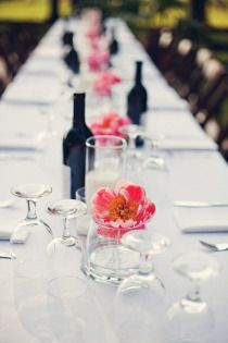 Lovely simple centrepieces. I love the simple white table with black red wine bottles and the punch of coral pink! I want this!