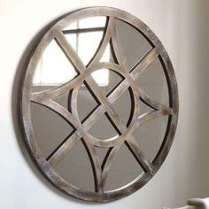 Circular wall mirror in rustic pine with an Old World compass design.   Product: Wall mirror        Construction Material: Hardwood solids, mirrored glass and pine veneers   Color: Rustic pine and worn white             Dimensions: 40 Diameter