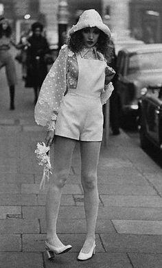Final do anos 60, início dos anos 70. Uso de um macacão com hotpants e uma camisa de manga presunto mostra a diferença entre as linhas do início dos anos 60, muito clean, com o fim desta década, princípio da próxima. O chapéu mostra também as formas mais relaxadas e orgânicas.