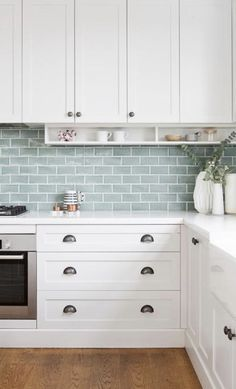 tiles Countertops White shaker drawers accented with dark nickel cup pulls are topped with a white marble countertop and positioned beside a stainless steel oven located beneath an integrated gas cooktop. Kitchen Wall Tiles, Kitchen Redo, New Kitchen, Kitchen Remodel, Kitchen Backsplash, Kitchen Splashback Ideas, Green Kitchen Walls, Splashback Tiles, Kitchen Counters