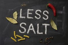 LESS SALT letters spices and herbs on a blackboard