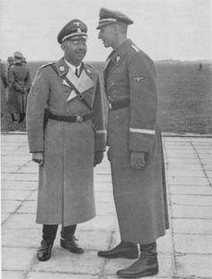 Reinhard Heydrich whispering something to Heinrich Himmler