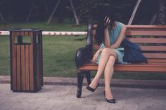 Woman sitting with her head in her hands on a park bench