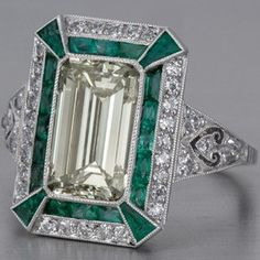 This emerald-cut diamond engagement ring in Art Deco style with emeralds is crafted in fine platinum.