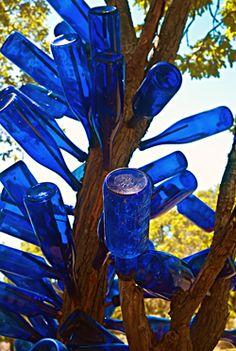 Bottle trees to keep the boogeyman away. Blue Glass Bottles, Blue Bottle, Bottles And Jars, Bird Bath Garden, Glass Garden, Garden Totems, Garden Whimsy, Garden Junk, Garden Sheds
