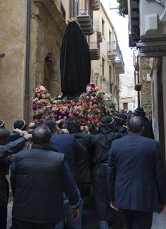 The procession heads up the street, with the town following behind.Picture of the Agrigento Venerdi Santo procession.