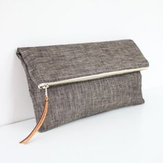"{30% OFF!} Normally $40. Are you as excited as we are?This simple clutch by Brighter Day is classy and clean, perfect for everyday use.  It features a sturdy metal zipper, a small interior pocket and faux leather zipper pull.  It is lined with black and white stripes. Measures 10.5"" across and 5.5"" tall (when folded over) and 9"" tall when open. Hurry and check out her site {by hurry, we mean run.. she has amazing products}:www.brighterday.etsy.com"