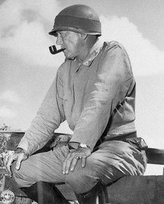 Lieutenant General George S. Patton sitting on a fence and smoking a pipe while observing 1941 maneuvers in Louisiana