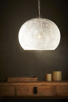 The coral pendants are crafted from perforated metal with a matte white raised and etched finish giving a delicate decorative porcelain appearance.