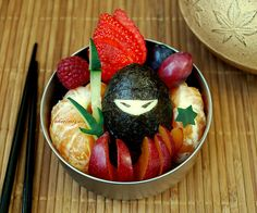 "Ninja In The Fruit Bento! by sherimiya ♥ of Happy Little Bento | ""A nori-wrapped hard-boiled egg ninja standing guard with his various weaponry. Watching over the satsuma mandarin, sugar plum, black grapes, strawberry and raspberry. Sword, dagger and throwing star shaped cucumber."" -Sherimiya"