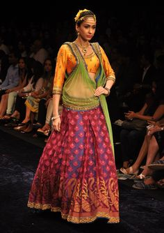 Purple brocade lehenga with saffron choli and green net dupatta.