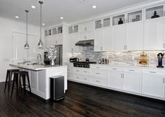 White and silver modern kitchen layout in Irvine, CA. Quartzite countertops, high-end stainless steel appliances, a 6-burner gas cooktop, a center island with seating, & decorative glass panel cabinets.