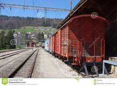 Photo about A classical image of a peeling red wooden caboose cargo car on a train in Switzerland on the tracks in a mountain station in a rural town. Image of mountain, side, view - 99024065 Switzerland, Train, Stock Photos, Image, Zug, Strollers