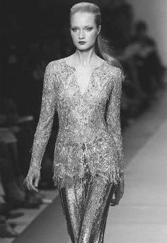 Fringed transparent top over silver metallic pants designed by Oscar de la Renta.
