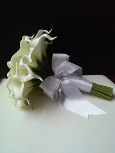 Elegant white 10x 11tall bridal bouquet with 36 Real Touch mini calla lilies. Handle is wrapped in white ribbon with a matching bow. *Calla lily and ribbon color can be customized, please contact me with any questions or special requests.  Ships in 1-2 weeks.  Also available: 8 wide x 11 tall bridesmaid bouquet with 24 mini calla lilies  Thank you so much for visiting my page!  Michele