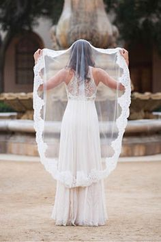 Bride with lace trimmed waltz veil in front of fountain
