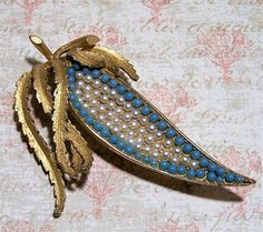 Mid Century BSK botanical brooch Faux pearls and round faux turquoise blue balls form the seed pod or leaf Etched gold tone setting Signed on back BSK 2 x 3 inches diameter Very good vintage condition, shows no wear International buyers welcome, over charges are refunded Priority shipping is optional 30117  Credit cards and Paypal accepted  Want to see more great pins? Click here: https://www.etsy.com/shop/GretelsTreasures?ref=seller-platform-mcnav&section_id&#x3D...