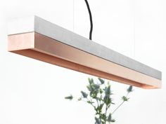 The rectangular pendant lamp is cast from a light gray concrete. It combines modern copper sheet with rough concrete into a timeless and elegant designer lamp. The different mate