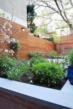 horizontal cedar plank fence, concrete patio and green flower beds