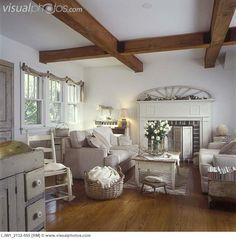 FAMILY ROOMS - Area off kitchen, neutral colors, shabby chic, light tan sofas, salvaged architectural accents, fireplace with wood shutters, white roses, wood floors, coffered beam ceiling, country modern, simple swag , antiques, distressed furniture