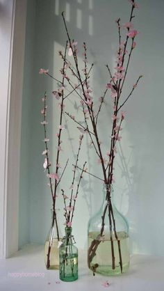 Cherry blossoms in Vintage glass bottles with pink butterflies by happyhomeblog.de