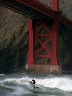 A Surfer is Dwarfed by the Northern End of the Golden Gate Bridge While Riding…