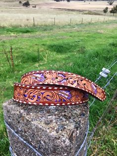 Hand carved metallic hide underlay floral/feather belt made by DustyCowgirl Leather  Like us on Facebook