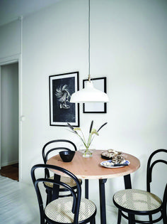 Black Thonet bentwood and cane cafe chairs at a small round kitchen table in a white Striking Monochrome Kitchen in A Warm Gothenburg Apartment Small Round Kitchen Table, Farmhouse Kitchen Tables, Small Tables, Kitchen Chairs, Cafe Chairs, Round Table With Chairs, Ikea Small Dining Table, Ikea Round Table, Table Stools