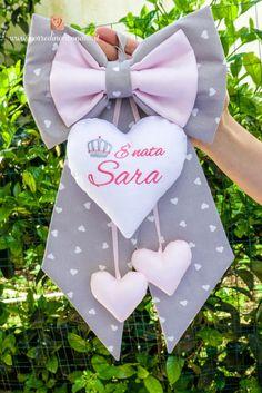 """Fiocco di cotone grigio a cuoricini bianchi e dettagli rosa, impreziosito dai ricami sul cuore centrale di una corona e della frase """"E' nata Sara""""."""
