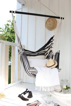 All white painted wood. Black and white tripes hammock. Summer living, how to make a small space stylish.