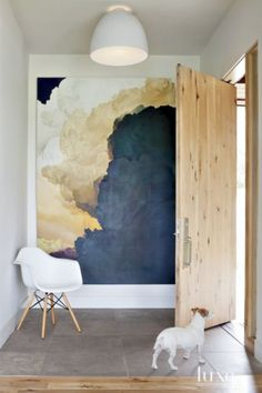 Architect Dale Hubbard designed a Boulder house marked by contemporary forms and rustic materials. For the entry, he chose a hickory pivot door by Deines Custom Door and Kansas limestone—to match the exterior— for the floor. The large-scale painting is by Ian Fisher, and the pendant is by Artemide.