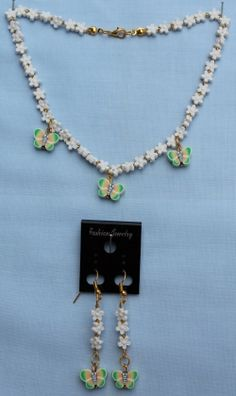 """This set is ideal for a child. It has white flower beads with gold lined seed beads and acrylic butterfly beads.  Necklace: 33cm (13"""")  Earrings: 4cm (1½"""") drop.  Materials used: Acrylic, glass and gold coloured metal."""