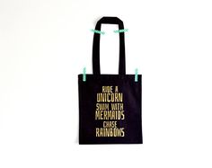 Items similar to Black tote bag with print Ride a unicorn swim with mermaids chase rainbows on Etsy Invisible Crown, Black Cotton, Unicorn, Reusable Tote Bags, Swimming, Trending Outfits, Rainbows, Mermaids, Unique Jewelry
